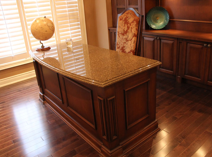 Custom home office with custom library unit and desk with granite countertop